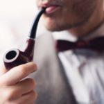 Close-up shot of an elegant man smoking pipe.